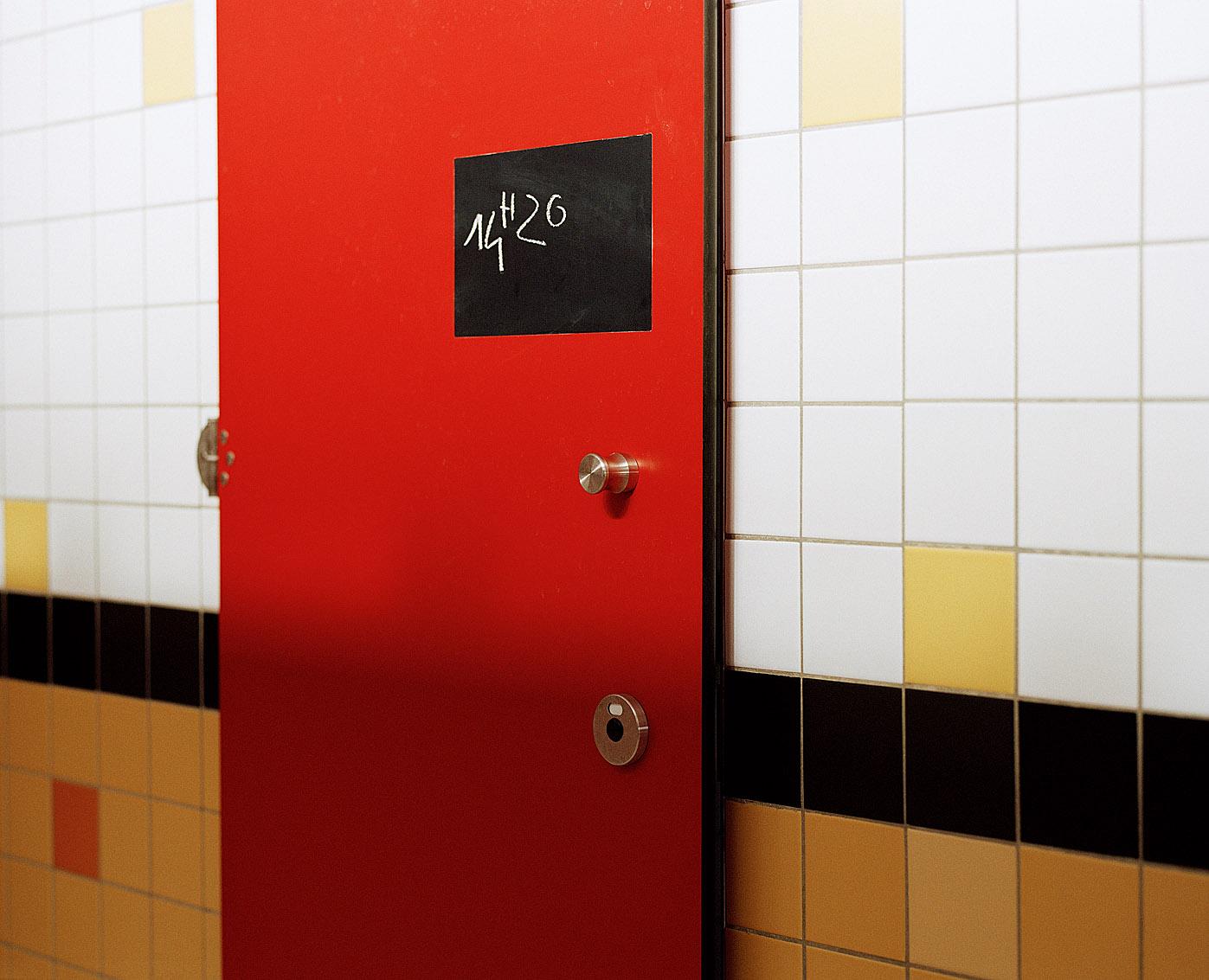 Le régisseur des bains inscrit l'heure d'arrivée de l'usager sur la porte de sa cabine. Bains-douches des Haies, Paris.