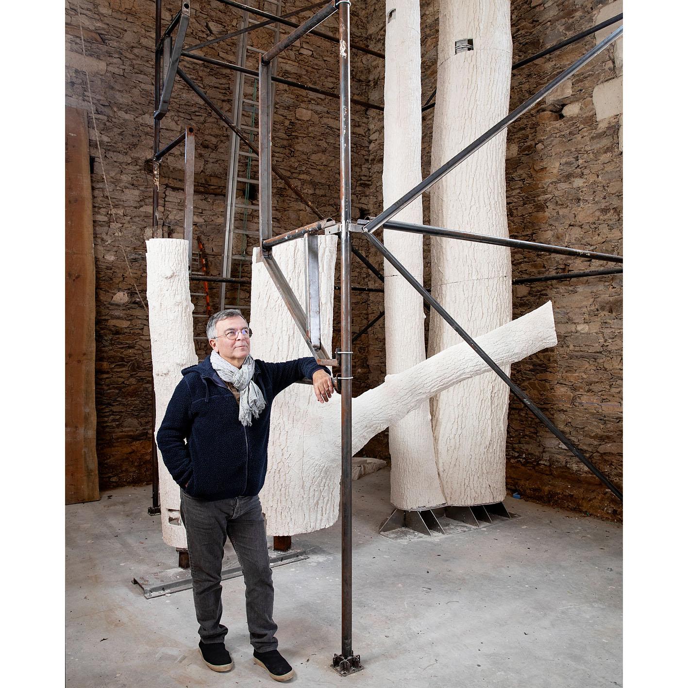 Fabrice Hyber au pied du moulage d'un chêne dans l'un de ses ateliers en Vendée.